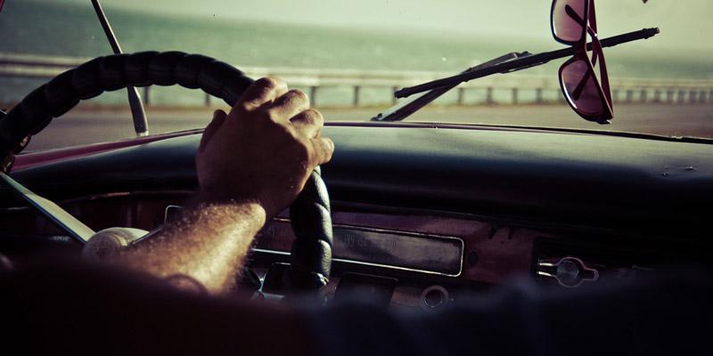 multas en verano, un brazo cogiendo el volante con el mar al fondo