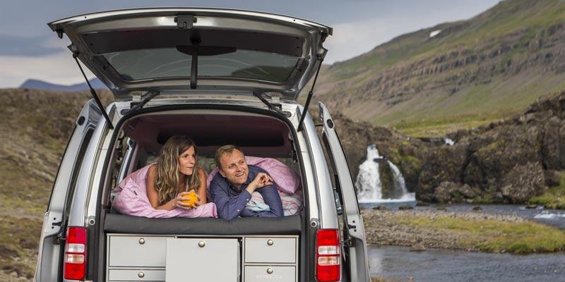 dormir en furgoneta, una pareja dentro de una furgoneta con la puerta trasera abierta y en medio de un paisaje natural de montaña