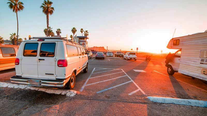 varias furgonetas y otros vehículos que están aparcados en un párquing con la apuesta de sol de fondo