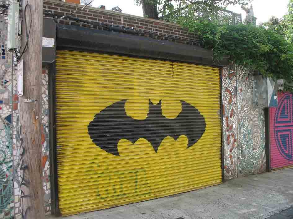 puerta de garaje amarilla con el emblema de batman en negro