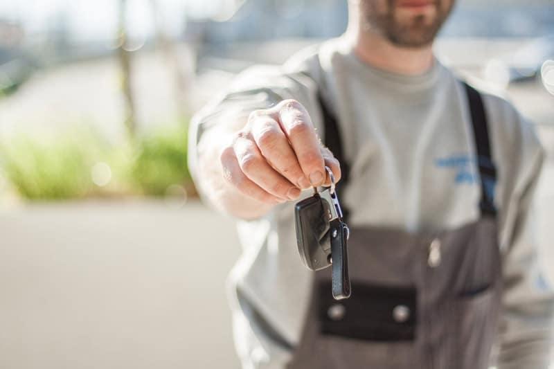 Un hombre ofreciendo unas llaves de un coche.